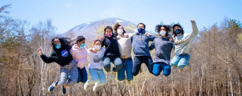 a group of ISAK students jumping with mount Asama in the background